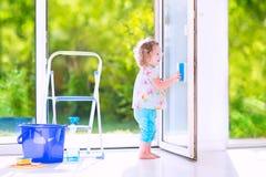 Schönes Mädchen, das ein Fenster im Reinraum wäscht Lizenzfreie Stockbilder