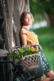 Schönes Mädchen, das ein hübsches Kleid mit dem Collegeblick hat Spaß im Park mit dem Fahrrad transportiert einen schönen Korb tr Stockfotografie