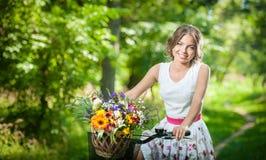 Schönes Mädchen, das ein nettes weißes Kleid hat Spaß im Park mit Fahrrad trägt Gesundes Lebensstilkonzept im Freien Recht blonde Stockbilder