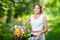 Schönes Mädchen, das ein nettes weißes Kleid hat Spaß im Park mit Fahrrad trägt Gesundes Lebensstilkonzept im Freien Recht blonde Lizenzfreie Stockfotografie