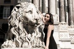 Schönes Mädchen, das ein schwarzes Kleid nahe bei gotischer Artlöwestatue trägt Stockbilder