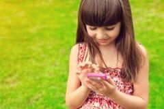 Schönes Mädchen, das ein Telefon auf einem Hintergrund des grünen Grases hält lizenzfreie stockfotografie