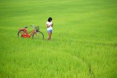Schönes Mädchen, das ein Telefon mit Fahrrad plaing ist Lizenzfreie Stockfotos