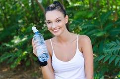 Schönes Mädchen, das eine Flasche Wasser anhalten lacht Stockbild