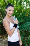 Schönes Mädchen, das eine Flasche Wasser O anhalten lächelt Stockbild