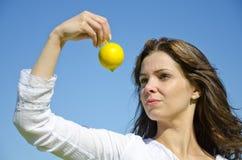 Schönes Mädchen, das eine frische Zitrone betrachtet lizenzfreie stockbilder