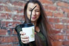 Schönes Mädchen, das eine Wegwerfkaffeetasse hält Lizenzfreie Stockfotografie