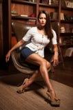 Schönes Mädchen, das in einem Lederstuhl sitzt Stockfotografie
