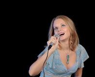 Schönes Mädchen, das in einem Mikrofon singt Stockbilder