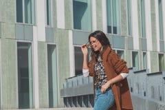 Schönes Mädchen, das in einem städtischen Zusammenhang aufwirft Stockfotografie