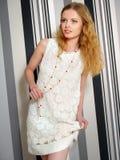 Schönes Mädchen, das in einem weißen gestrickten Kleid aufwirft stockfotografie