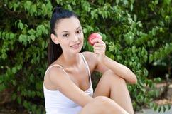 Schönes Mädchen, das einen roten Apfel anhält Stockfoto