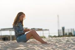 Schönes Mädchen, das einen Smartphone in den Händen auf dem Strand nahe dem Seeufersand im Hintergrund hält Lizenzfreie Stockbilder