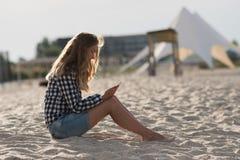 Schönes Mädchen, das einen Smartphone in den Händen auf dem Strand nahe dem Seeufersand im Hintergrund hält Lizenzfreie Stockfotos