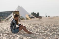 Schönes Mädchen, das einen Smartphone in den Händen auf dem Strand nahe dem Seeufersand im Hintergrund hält Stockfoto