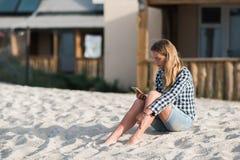 Schönes Mädchen, das einen Smartphone in den Händen auf dem Strand nahe dem Seeufersand im Hintergrund hält Stockfotografie