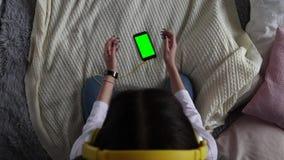 Schönes Mädchen, das einen Smartphone in den Händen eines grünen Schirmgrünschirmes hält stock footage