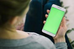 Schönes Mädchen, das einen Smartphone in den Händen eines grünen scre hält Stockbild