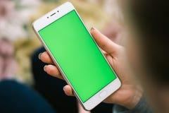 Schönes Mädchen, das einen Smartphone in den Händen eines grünen scre hält Lizenzfreie Stockbilder