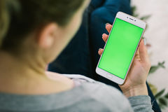 Schönes Mädchen, das einen Smartphone in den Händen eines grünen scre hält Lizenzfreie Stockfotografie