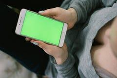 Schönes Mädchen, das einen Smartphone in den Händen eines grünen scre hält Stockbilder