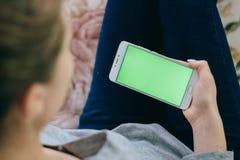 Schönes Mädchen, das einen Smartphone in den Händen eines grünen scre hält Lizenzfreies Stockbild