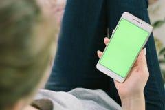 Schönes Mädchen, das einen Smartphone in den Händen eines grünen scre hält Stockfotos