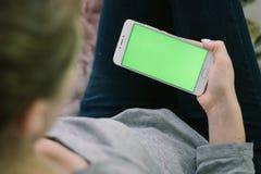 Schönes Mädchen, das einen Smartphone in den Händen eines grünen scre hält Lizenzfreie Stockfotos