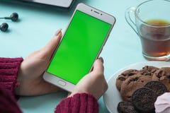 Schönes Mädchen, das einen Smartphone in den Händen eines grünen scre hält Stockfotografie