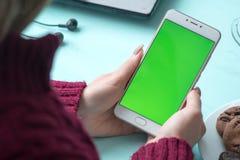 Schönes Mädchen, das einen Smartphone in den Händen eines grünen scre hält Stockfoto
