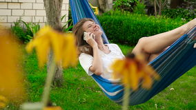 Schönes Mädchen, das in einer Hängematte liegt Er spricht auf dem Telefon und dem Lachen HD stock footage