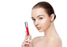 Schönes Mädchen, das flüssigen roten Lippenstift hält Lizenzfreie Stockfotos