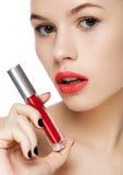 Schönes Mädchen, das flüssiges rotes Lippenstiftrohr hält Stockbilder