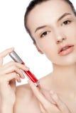 Schönes Mädchen, das flüssiges rotes Lippenstiftrohr hält Stockfoto