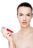 Schönes Mädchen, das flüssiges rotes Lippenstiftrohr hält Lizenzfreie Stockbilder