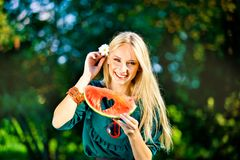 Attraktive blonde Frau, die Wassermelone im Freien hält Stockfoto