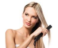 Schönes Mädchen, das Frisur mit Haareisen bildet Stockfoto