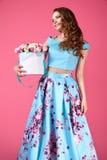 Schönes Mädchen, das großen Blumenstrauß von Papierblumen im Kasten hält Lizenzfreie Stockfotos
