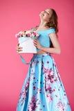 Schönes Mädchen, das großen Blumenstrauß von Papierblumen im Kasten hält Stockfotos
