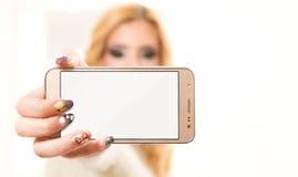 Schönes Mädchen, das Handy mit leerer Anzeige zeigt Stockfoto