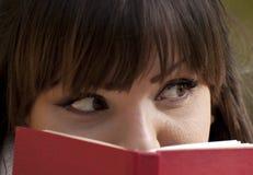 Schönes Mädchen, das hinter einem Buch sich versteckt Stockfoto