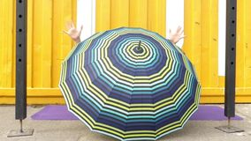 Schönes Mädchen, das hinter einem Regenschirm sich versteckt stock footage
