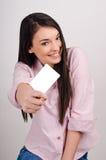Junge Frau, die eine leere Visitenkarte halten lächelt. Stockfotos