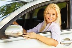 Schönes Mädchen, das ihr neues Auto genießt Stockfoto