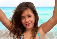 Schönes Mädchen, das ihre Arme an einem Strand anhebt Stockfoto