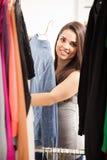 Schönes Mädchen, das ihre Garderobe betrachtet Stockbild