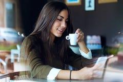 Schönes Mädchen, das ihren Handy im Café verwendet Stockbilder