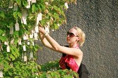Schönes Mädchen, das ihren Wunsch auf einem Wunschbaum hängt Lizenzfreies Stockbild