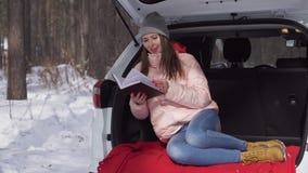 Schönes Mädchen, das im Auto, ein Tagebuch, das Lächeln und das Lachen lesend sitzt stock footage
