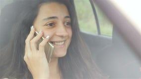 schönes Mädchen, das im Auto sitzt und am Telefon spricht Schönes Lächeln auf ihrem Gesicht Nahaufnahme stock video